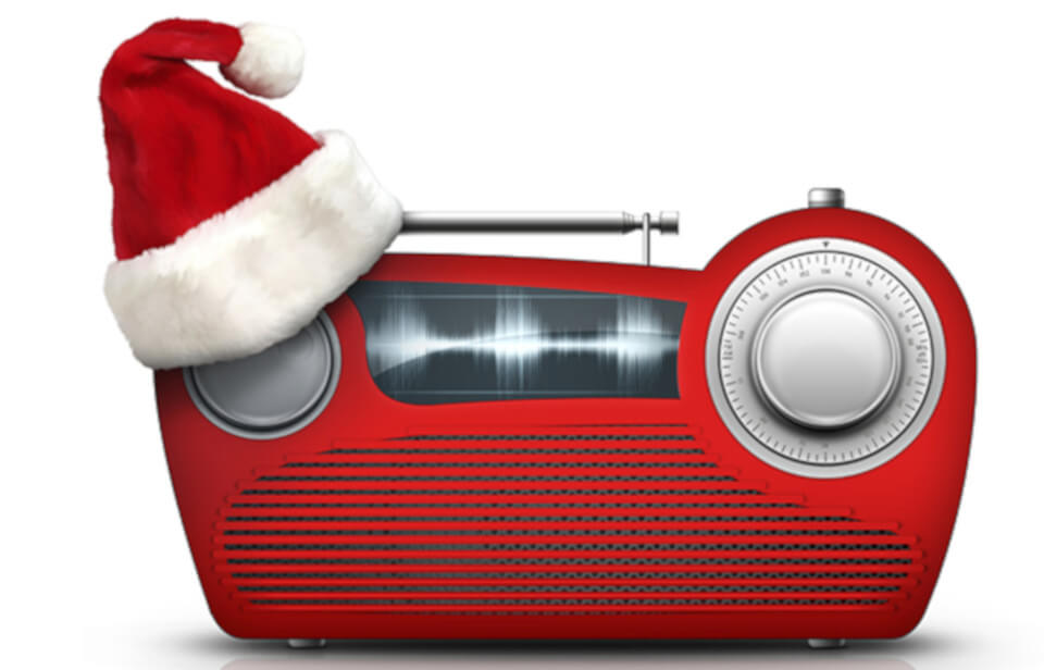An old school red radio wearing a christmas hat