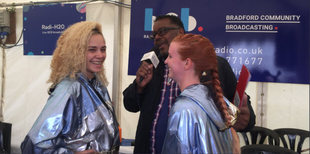 Two people in silver capes being interviewed
