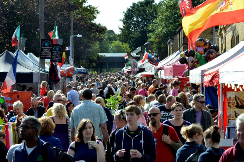 a large moving crowd of people walking down a road with marquees and tents on either side