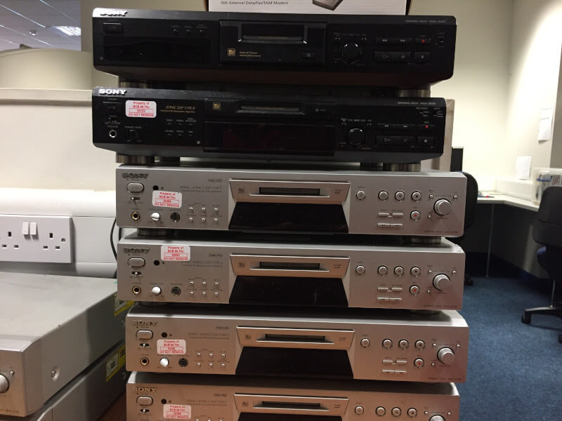 a stack of worn-looking minidisc players