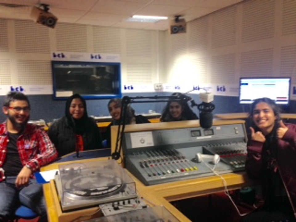 A group of young people sitting by the mixing desk in a recording studio looking really happy to be broadcasting