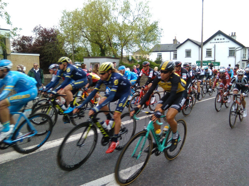 A motion blurred photo of a large school of cyclists on a road