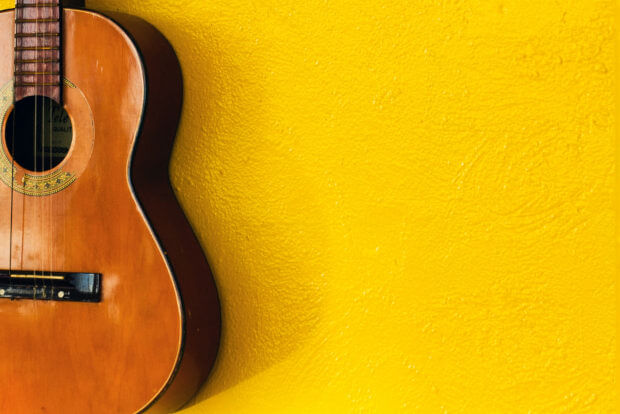 A partial photo of an acoustic guitar over a yellow wall background