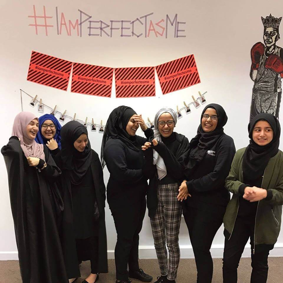 Young adult females in modern black attire and hijabs smiling #iamperfectasme