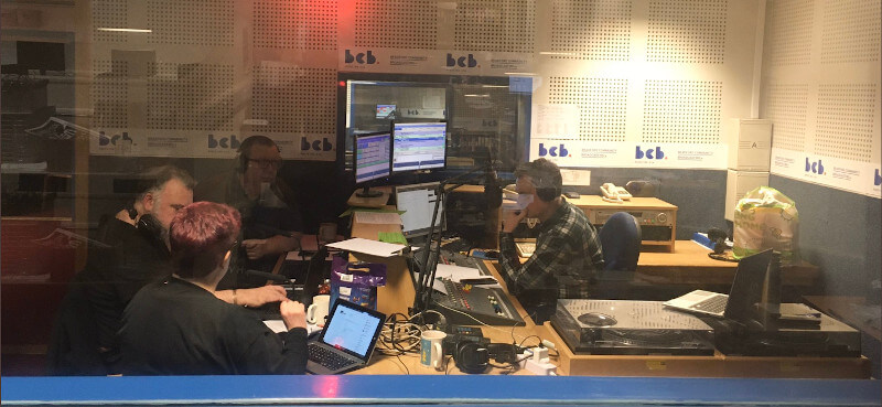 A photo of a group of people sitting around the radio recording desk