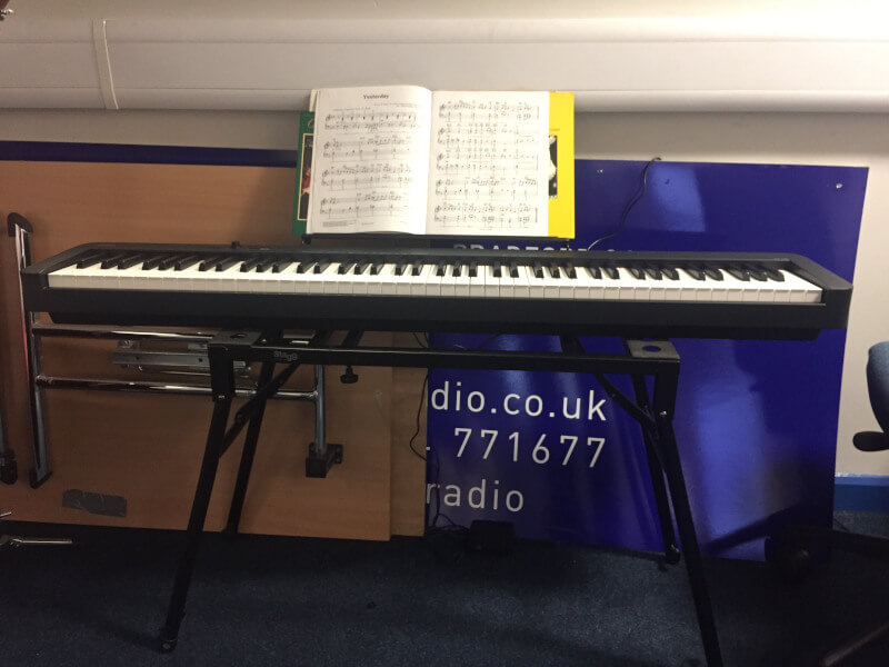 A lovely looking digital piano with music scores laid out above the keyboard
