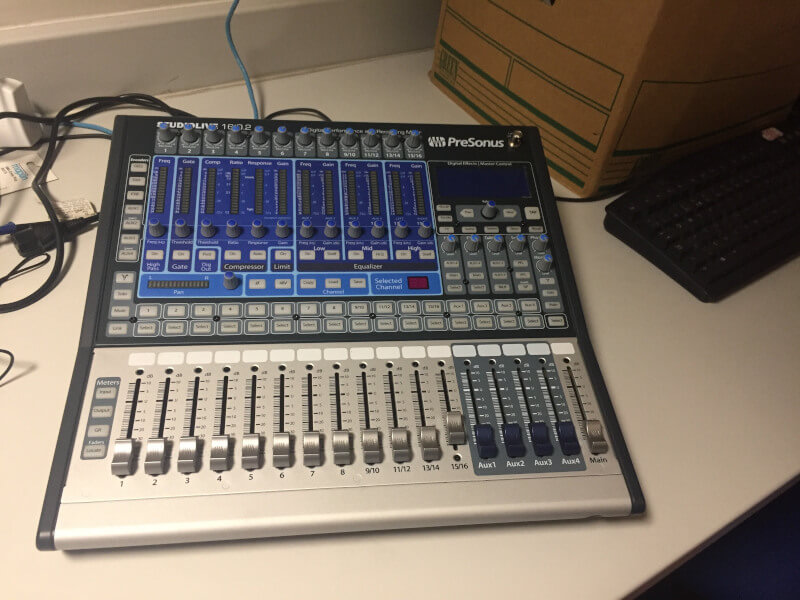 An audio mixing desk full of buttons, faders and inputs