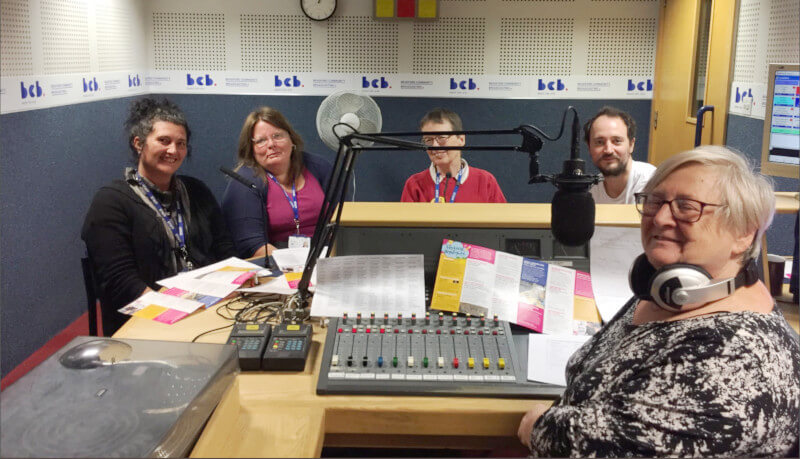 A smiling person with glasses and headphones driving the studio desk with four guests on the other side of the desk