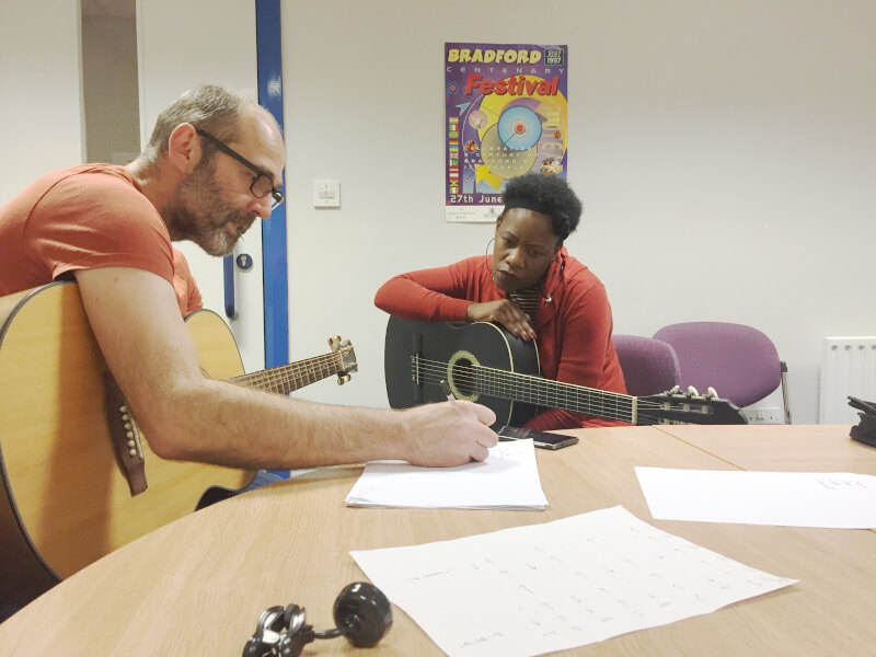 A person with glasses holding a guitar is writing something for another person holding a guitar to look at