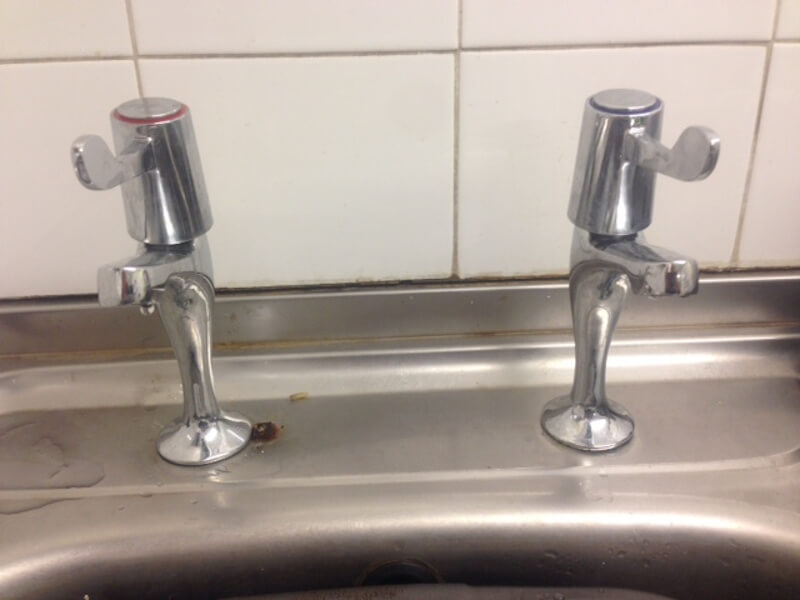 Two silver taps, one with a red band and the other blue, infront of white kitchen tiles