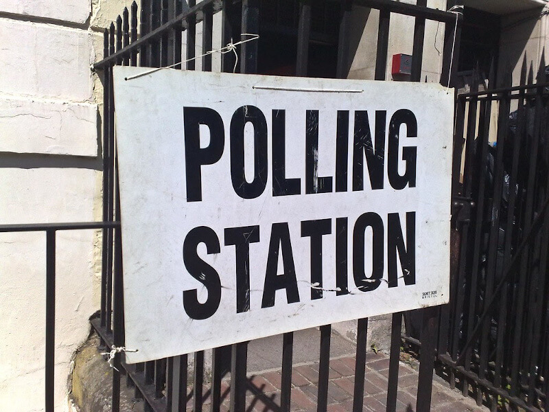 a white board with large black letters POLLING STATION tied to black metal spikey fence