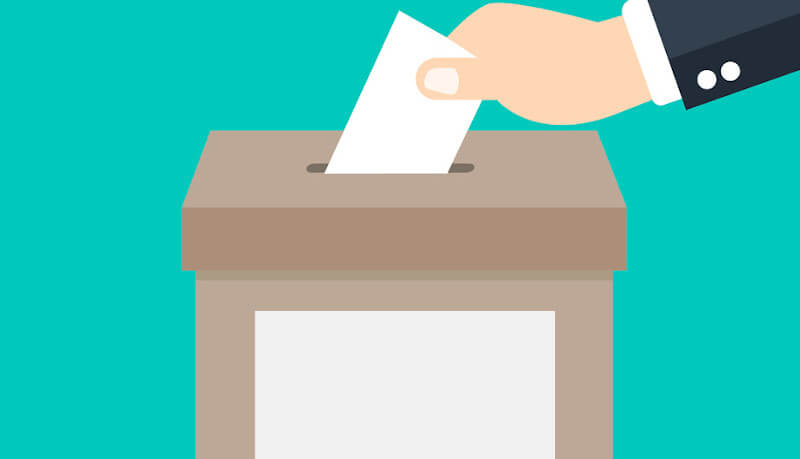 A cartoonish illustration of a presumably white man in a suit putting their vote in a ballot box