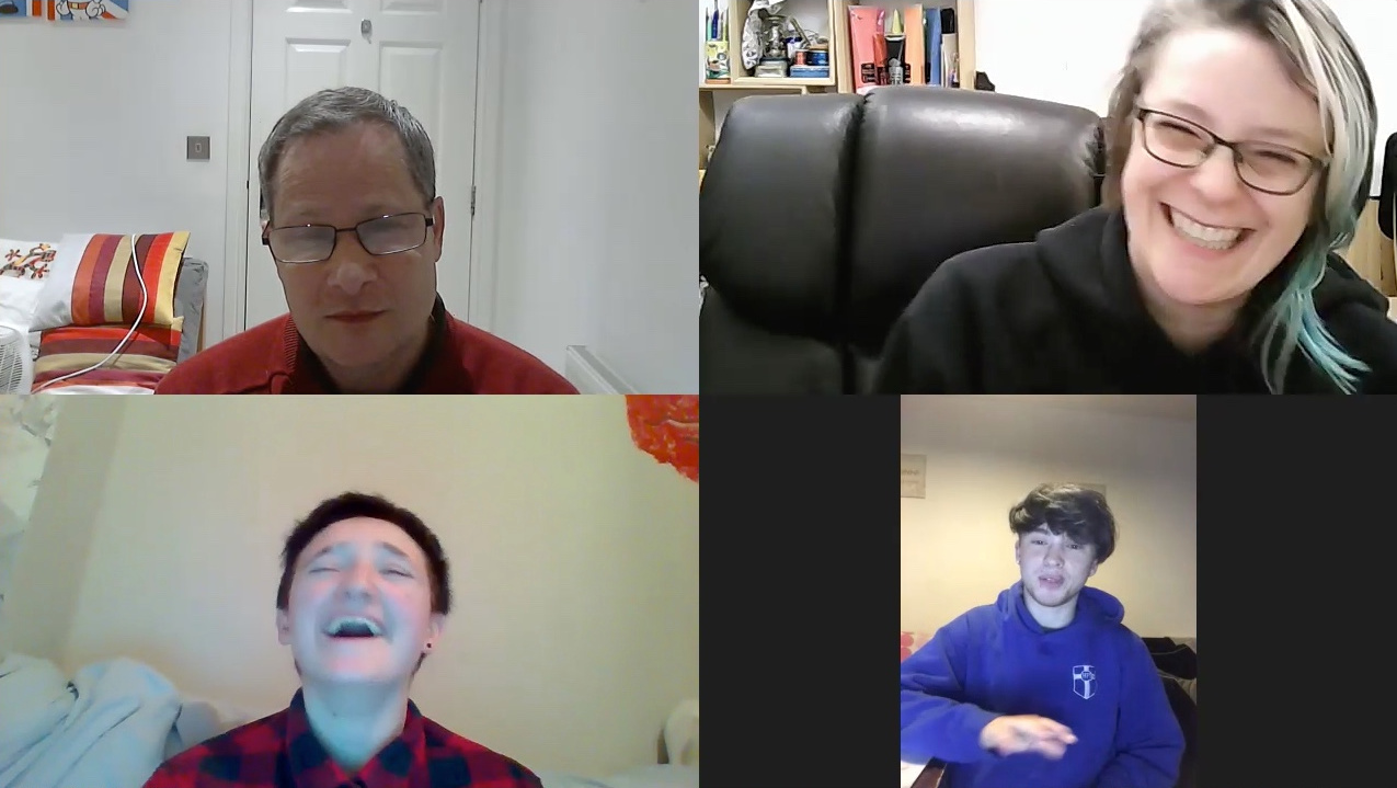 A zoom call photo of 4 happy and laughing people within their separate screens having a virtual conference