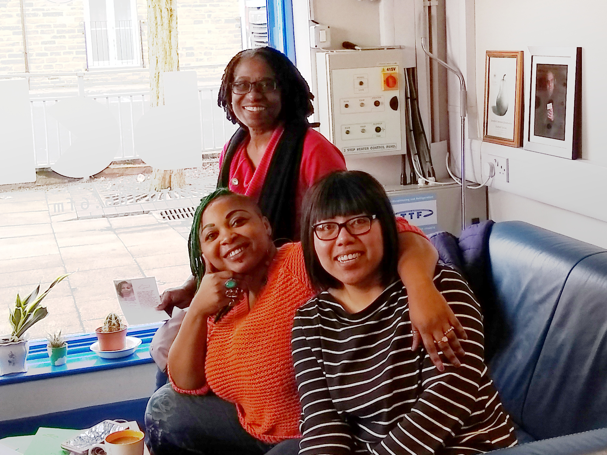 Maureen, Kafayat and shi group photo on a blue couch