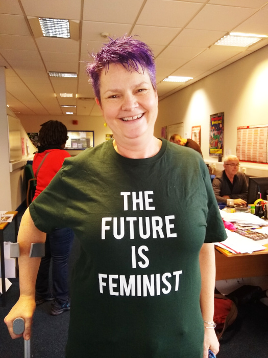 Grinning lady with purple hair wearing a green tshirt that says The Future is Feminist