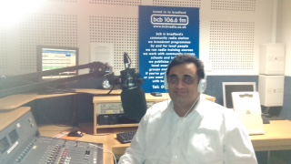 Naeem Nawaz behind the desk